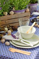 Garden table set with purple tablecloth, white crockery, mussel shells and snail shells
