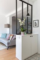 Partition made from interior window with black frame on top of white cabinet
