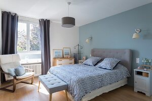 Bedroom with pastel-blue accent wall and grey upholstered headboard