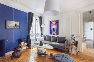 Retro living room with blue accent wall in renovated period apartment