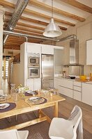 Set dining table in front of white fitted kitchen counter in open-plan, high-ceilinged interior with ventilation ducts