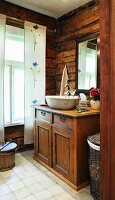 Rustic bathroom with countertop sink on top of old cabinet