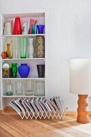 Colourful glass vases on shelves in niche behind magazine rack and floor lamp