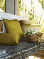 Cushions, boxes and bowls on weathered bench