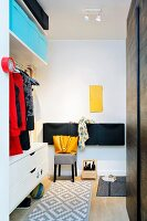 Fitted cabinets and storage boxes in hallway with small yellow inspection door on white wall