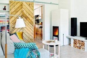 Gemütlicher Wohnbereich mit Kaminfeuer, Blick auf rustikale Schiebetür zur Küche