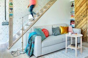 Restaurierte Holztreppe in Wohnraum mit Couch und Upcycling-Schiebetür