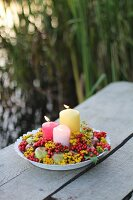 Autumnal arrangement of candles, berries, apples and flowers on outdoor table