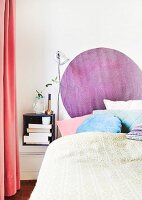 Round purple rug hung on wall above head of bed
