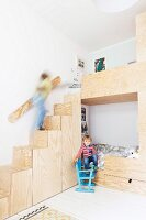 Children playing on custom bunk beds with storage steps