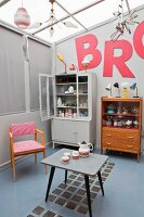 Collection of retro furniture below red letters on wall