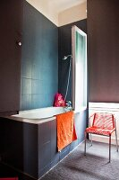 Dark tiles and walls in bathroom with red accents