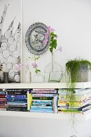 Several stacks of books on wall-mounted shelf and delicate flower arrangements below decorative wall plate