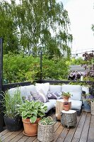 Pallet couch and tree stump stool on castors on summery terrace