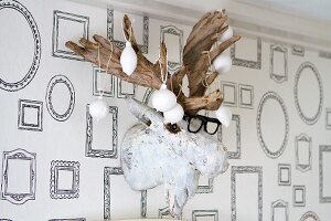 Christmas-tree baubles dipped in plaster and hung from fake moose head on wall