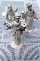 Christmas crib figurines dipped in plaster drying on newspaper