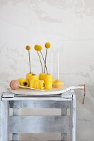 Craspedia arranged in reels of yellow thread next to cake pops