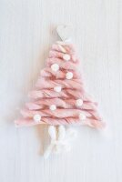 Christmas tree formed from sections of pink wool on white surface