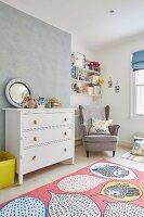 Kinderzimmer mit Ohrensessel und weißer Schubladenkommode