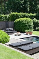 Loungers next to pool in well-tended garden
