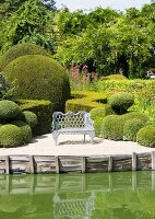 Baroque metal bench amongst clipped box hedges next to lake