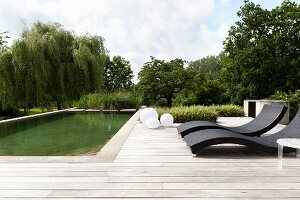 Designer sun loungers on wooden deck adjoining pool