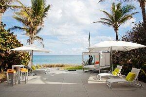 Verschiedene Liegen auf moderner Terrasse unter Palmen