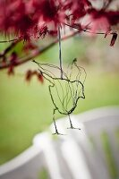 Delicate hand-made wire bird hung from branch
