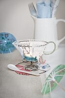 Teacup-shaped tealight holder hand-made from wire and lace on table