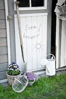Lettering and sun made from bent wire on wooden door flanked by potted violas, spade and watering can