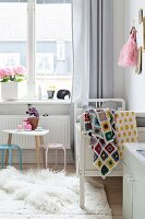 Crocheted patchwork blanket on white cot and small table and chairs in girl's bedroom
