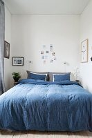 Blue bed linen on double bed and various photos decorating walls of narrow bedroom
