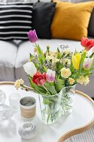 Colorful spring flowers in glass Aalto vase on organically formed coffee table