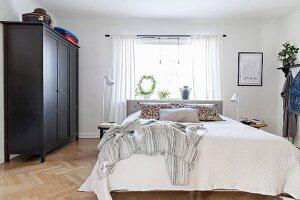 Black wardrobe, herringbone parquet floor and bed below window in bedroom