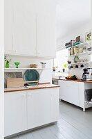Board floor in white Scandinavian kitchen
