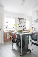 White board floor and island counter on castors in Scandinavian kitchen
