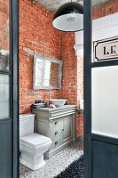 Vintage-style furnishings and brick walls in bathroom