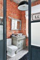 Badezimmer mit nostalgischem Mobiliar und Backsteinwand