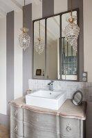 Sink on antique Gustavian-style cabinet below wall-mounted mirror