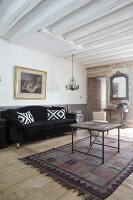 Scatter cushions on black velvet sofa, vintage coffee table and white wood-beamed ceiling in living room