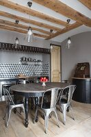 Oval table and classic chairs in front of kitchen counter built into large niche in wall