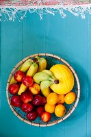 Round basket of fruit on blue wooden floor
