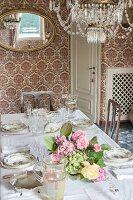 Festlich gedeckte Tafel mit Blumenbouquet im Salon