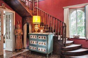 Alte Kommode mit Leuchte und Heiligenfigur vor alter Holztreppe
