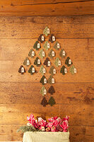 Advent calender made from crocheted fir trees on wooden wall