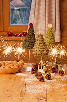 Tiny crocheted Christmas trees and sparklers on wooden table