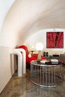 Designermöbel in Wohnbereich mit Gewölbedecke und Betonboden