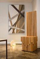 Moderner Thronstuhl aus Holz vor Kunst mit Schnüren