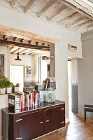 Retro living area with aperture in wall and rustic wood-beamed ceiling