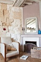 Armchair next to open fireplace in restored country house
